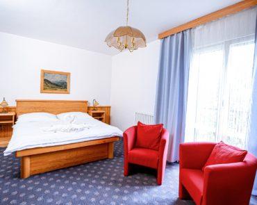 Ložnice s manželskou postelí v apartmánu Prezident